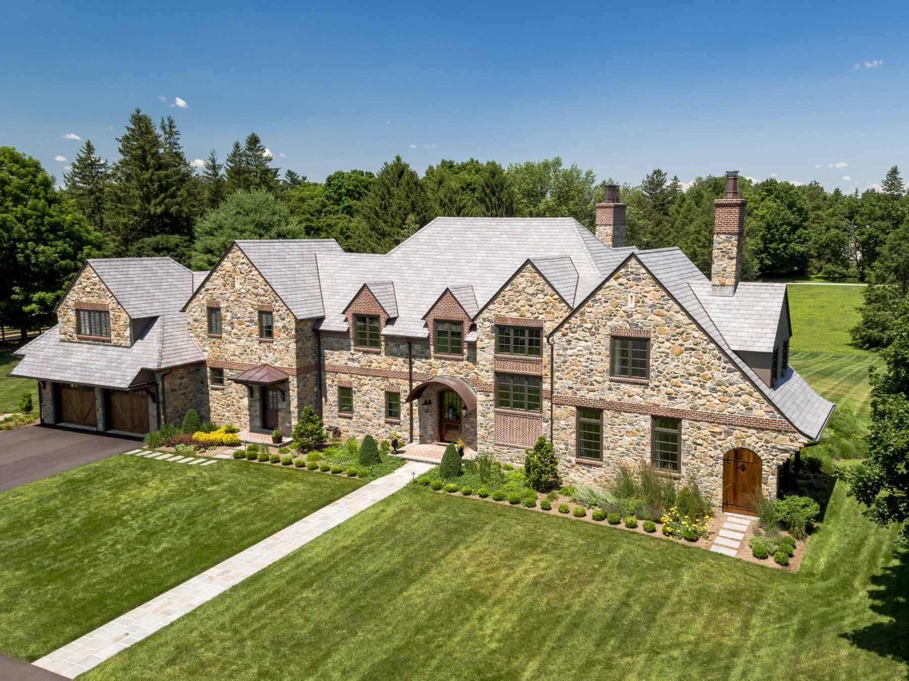 English Country House Inspired Greenville Home front elevation drone